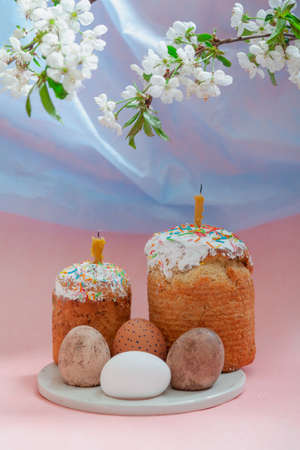 Easter still life. Two Easter cakes and eggs stand on a round stand on a pink background. Candles are inserted into the Easter cakes. Top view blue fabric symbol sky and branch with white flowers