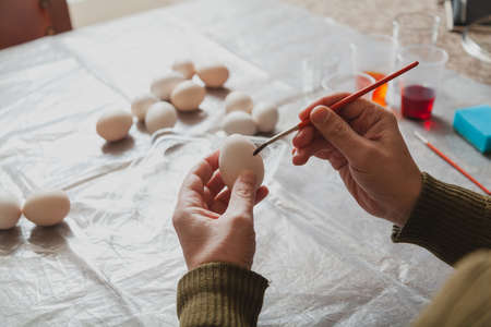 Preparing for the holiday of Easter. Male hands color chicken eggs on the dining table at home