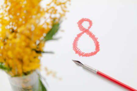 Eighth of March is a women's holiday. On a white background, a drawn number 8 in red. On the left is an out-of-focus image of a yellow mimosa. Nearby lies a vintage fountain pen