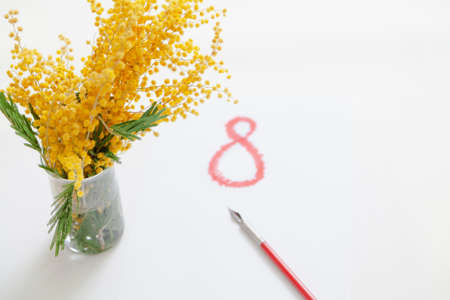 Festive spring still life. A branch of yellow mimosa stands in a glass vase on a white background. Next to it is the drawn number 8 in red. Nearby lies a vintage fountain pen
