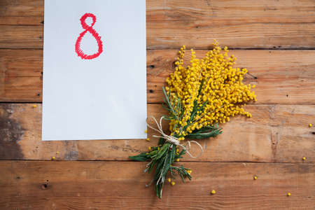 March 8 women holiday. A bouquet of yellow mimosa with green leaves lies on wooden boards. Nearby lies a white sheet of paper with a drawn red number 8