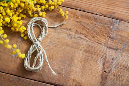 March 8 is a spring holiday. The number 8 made of rope lies on wooden boards close-up. Nearby lies a branch of yellow mimosa