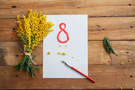 Spring still life. On a white sheet of paper, the number 8 is drawn in red. On the left is a bouquet of yellow mimosa. Nearby lies a vintage fountain pen Stockfoto