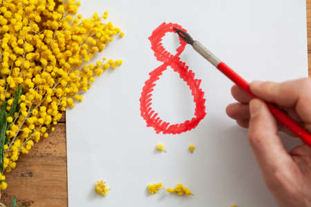 DIY gift. The right hand draws a large red number 8 on a white sheet of paper with an antique fountain pen. On the left is a branch of yellow mimosa. Close-up Stockfoto