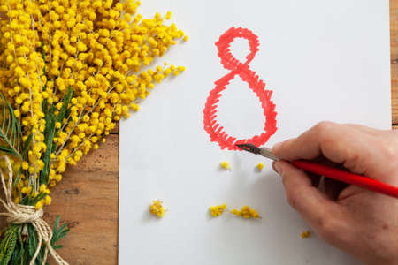 right hand draws a large red number 8 on a white sheet of paper with an antique fountain pen. The sheet lies on wooden boards. On the left is a branch of yellow mimosa Stockfoto
