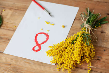 Eighth of March is a women's holiday. On a white sheet of paper, the number 8 is drawn in red. On the right is a bouquet of yellow mimosa. Nearby lies a vintage fountain pen