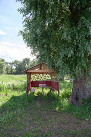 Gazebo in nature. A wooden gazebo stands next to a large tree. Inside there is a wooden table and benches Stockfoto