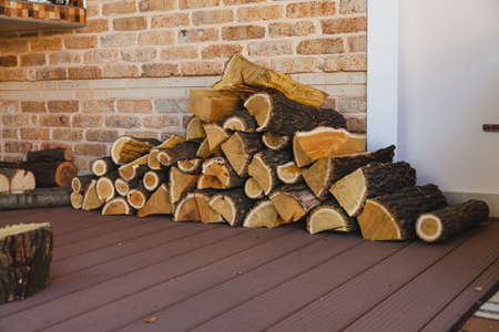 Firewood tree mulberry pyramid stacked pyramid in front of brick wall on veranda Reklamní fotografie