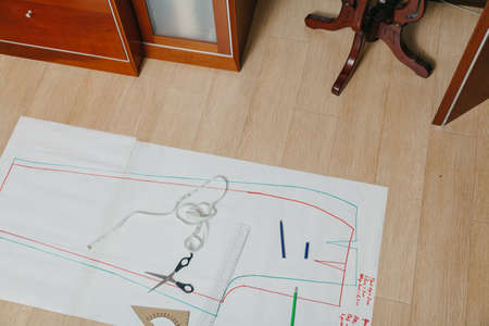 Sewing pattern lies on the floor. A silhouette of a garment is drawn on a paper sheet. On top is a ruler, scissors and a flexible centimeter