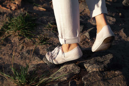 Walking along the beach. Female legs in white trousers and shoes go over stones on a sandy beach close up Reklamní fotografie