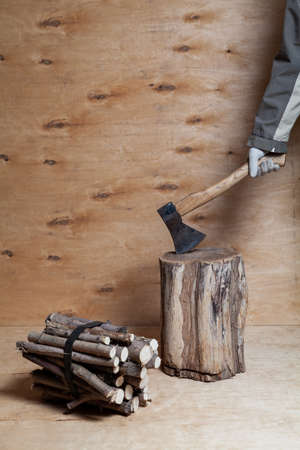 hand in a white glove stuck an ax into a stump against a background of light-colored plywood. Nearby lies a bundle of round firewood. There is a place for an inscription