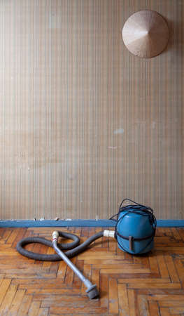 antique vacuum cleaner with a long hose sits on a scratched parquet floor. Above him on the wall is an Asian conical hat Reklamní fotografie - 166469958