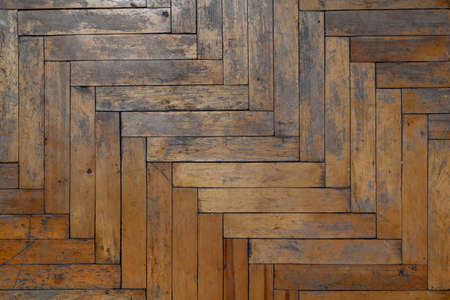 Old parquet floor close up. Paint and varnish are peeling off the wooden planks. View from above