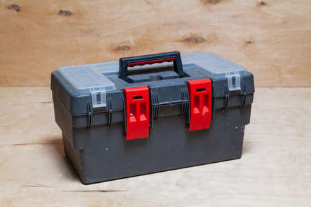 modern plastic closed toolbox stands against a light plywood background Reklamní fotografie - 166468430