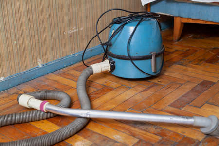 antique vacuum cleaner with a long hose sits on a scratched parquet floor in front of a wall. There is a wooden bed in the back