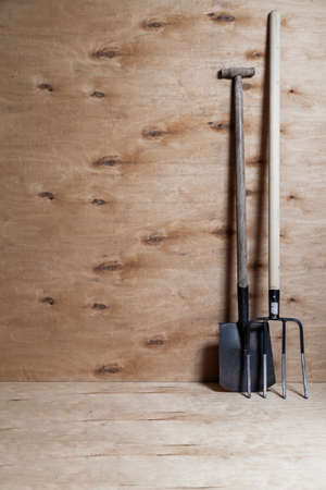 shovel and black metal pitchfork on a long wooden handle stand upright against a light plywood background