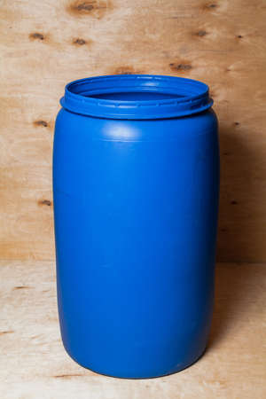 blue round plastic container without a lid stands against a background of light plywood
