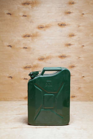 green metal canister stands against a background of light plywood
