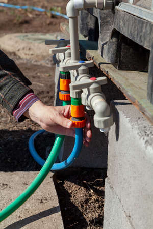 Installation by an irrigation system. A hand winds a hose on the plastic pipes of the garden watering system. A container with water is installed above the pipes