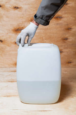 hand in a white glove unscrews the lid on a white plastic canister against a background of light plywood. The container is filled with liquid