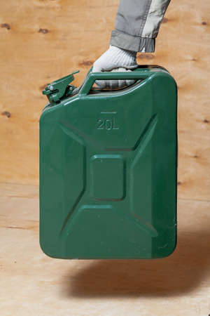 hand in a work glove holds a green metal canister on a light plywood background