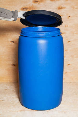 White gloved hands hold a black lid over a blue circular plastic container against a light plywood background Reklamní fotografie
