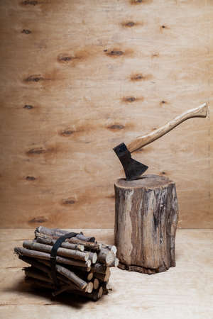 Ax and firewood. The ax sticks out in a stump against a background of light plywood. Nearby lies a bundle of round firewood. Stains are visible on a vertical plywood sheet Reklamní fotografie