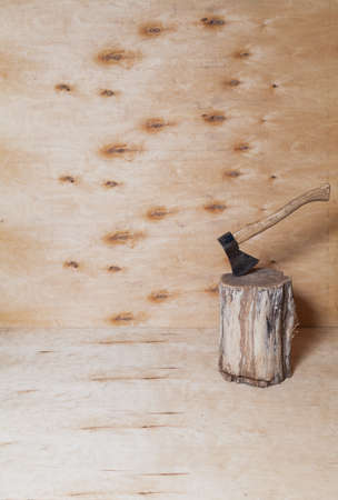 ax sticks out in a stump against a background of light plywood. Stains are visible on a vertical plywood sheet Reklamní fotografie