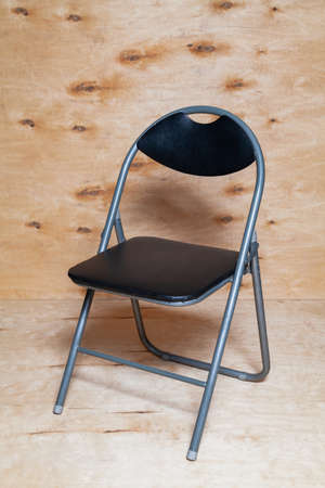 Art Nouveau folding chair stands against a background of light plywood. The chair has an arched back and a black seat
