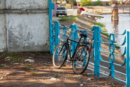 black bicycle stands in front of a blue metal fence on the river bank. Before him is a stone wall