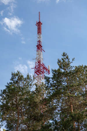 tall metal lattice tower for the transmission of a television signal stands against the backdrop of a blue sky. Bottom view. Tall green trees grow under it Reklamní fotografie - 166468101