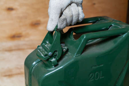 hand in a work glove opens the lid on a green metal canister against a background of light plywood close-up