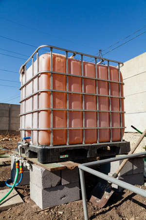 plastic container for irrigating the garden stands on the stones above the soil. The container is placed in a metal grid