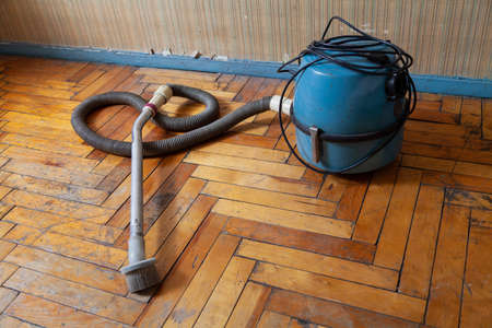 antique vacuum cleaner with a long hose stands on a scratched parquet floor in front of a wall Reklamní fotografie