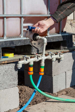 Irrigation system management. A hand opens a tap on the plastic pipes of the garden watering system. A container with water is installed above the pipes Reklamní fotografie