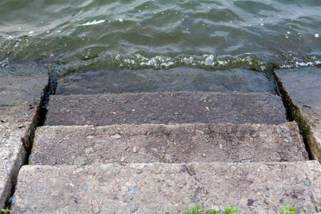Entering the water. A wide, gently sloping stone staircase descends into the water. Sloped concrete slabs on the sides