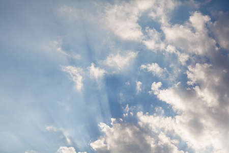 Cloud and rays of light. Parallel rays of light shine through a white fluffy cloud against a blue sky Фото со стока