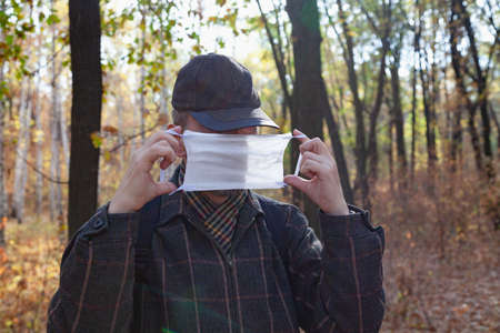 man in a cap puts on a white medical mask in a spring forest Standard-Bild