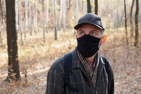man in a cap and a black medical mask stands in a spring forest. Behind a birch grove Standard-Bild