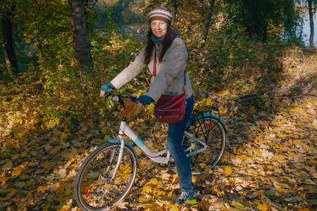 Beautiful young woman in a beret with long red hair is sitting on a bicycle in an autumn park. Around the fallen leaves
