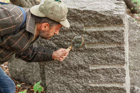 geologist examines a large piece of gray rock through a large magnifying glass on a bone handle. Traces of holes are visible on the stone Standard-Bild