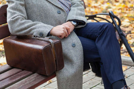 man in an unbuttoned gray coat sits on a wooden bench. Nearby is a brown leather carpetbag in retro style