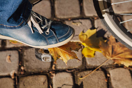Leg in a blue leather sneaker on a bicycle pedal. Below it is a yellow maple leaf. Near the tile are yellow fallen leaf