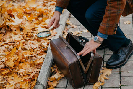 man in a checkered jacket pulled out a magnifying glass from a brown carpetbag on the alley of an autumn park close-up. View from above