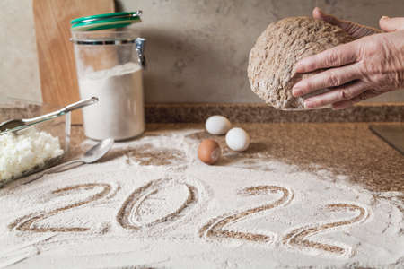 New Year in the kitchen. 2022 is written in flour. Hands are holding a piece of dough. Eggs and a glass bowl on a granite countertop