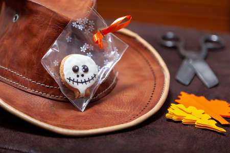 Merry Halloween. Round Halloween biscuits in a package lie on a leather hat. Nearby lie the paper leaves of oak and maple Standard-Bild
