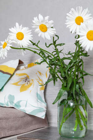 bouquet of large daisies stands in a transparent vase on the bedside table next to the bed. On the bed are two pillows