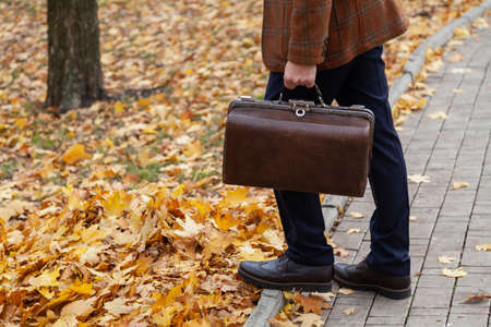 gentleman in a stylish checkered jacket stands in the alley of the square in the fall afternoon. Holding a vintage carpetbag in his hand. Close-up