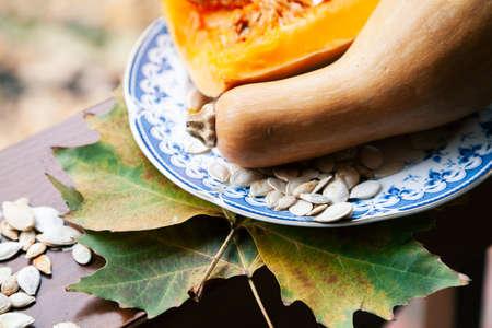 Autumn still life. An elongated pumpkin and white seeds lie on a plate. Maple leaves lie on a wooden railing Standard-Bild
