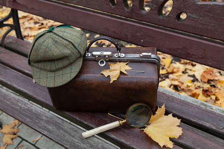 Detective set. There is a leather valise on a wooden bench in the park. He is wearing a green cap. Nearby lies a large magnifying glass and yellow maple leaves